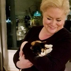 一个女人抱着一只白布小猫铲屎官们都好奇?如何正确抱猫?
